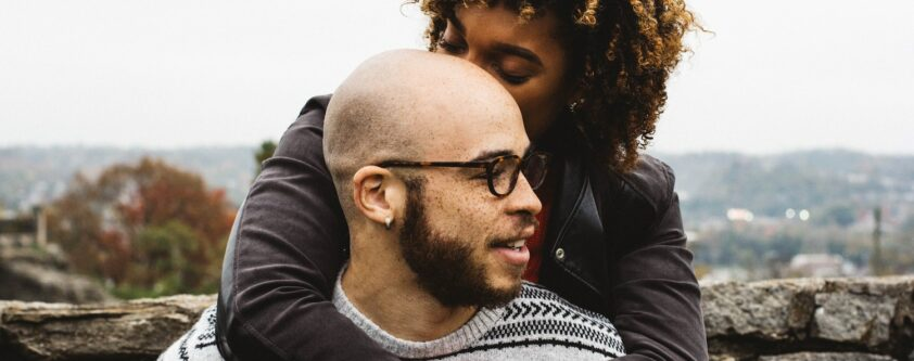 FLBBA Black couple with woman on man's back kissing his head