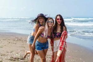three women on beach smiling at camera
