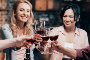 women clinking wine glasses together