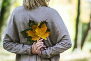 Woman holding fall leaves behind back