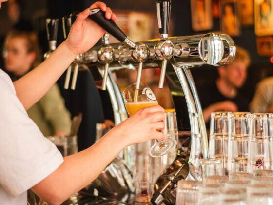 beer from tap being poured into glass in crowded bar