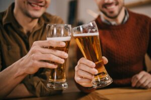 two men clinking beer glasses seated at bar
