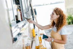 red-haired woman passing money through food truck window with beer on counter